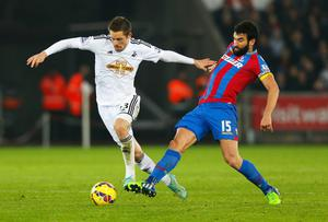 Swansea City midfielder Gylfi Sigurdsson holds off a challenge from Crystal Palace captain Mile Jedinak during their Premier League clash at the Liberty Stadium. Photo: Harry Engels/Getty Images