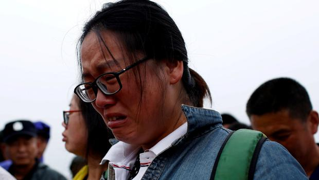 A relative of a missing passenger aboard a capsized ship cries on the banks of the Jianli section of Yangtze River in Hubei province, China, June 4, 2015. REUTERS/Aly Song