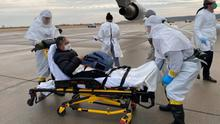 Fever: Carl Goldman on a stretcher after touching down at the University of Nebraska's hospital where he has been kept in quarantine