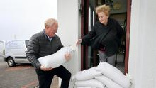 Sea defences: Padraic Conroy places sandbags at the home of his mother Kay (90) in the Claddagh, Galway. Picture: Frank McGrath