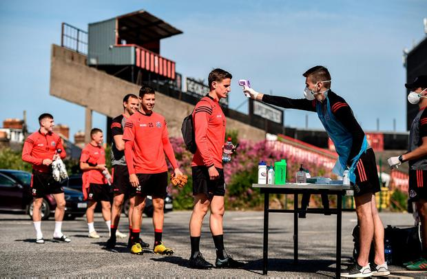 Paddy Kirk has his temperature taken by Aaron Fitzsimons, Equipment Manager, as his team-mates wait in line ahead of a Bohemian FC training session at Dalymount Park. Photo: Sam Barnes/Sportsfile