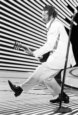 Chuck Berry performs his famous 'duck walk' as he plays his guitar on stage in 1980. Photo: AP