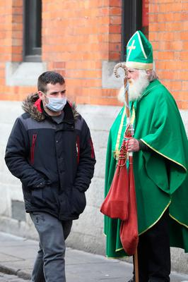 A man in a face mask walks past a man dressed as St Patrick near the Temple bar in Dublin, on St Patrick's day. PA Photo. Picture date: Tuesday March 17, 2020. See PA story HEALTH Coronavirus. Photo credit should read: Niall Carson/PA Wire