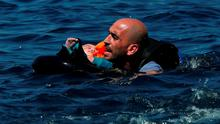 A Syrian refugee holding a baby in a lifetube swims towards the shore after their dinghy deflated some 100m away before reaching the Greek island of Lesbos, September 13, 2015