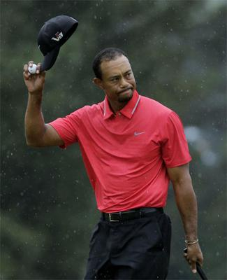 Tiger Woods tips his cap after putting out on the 18th hole during the fourth round of the Masters golf tournament