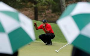 Tiger Woods lines up a putt on the eighth green
