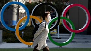 A woman wearing a protective face mask, following an outbreak of the coronavirus disease (COVID-19), walks past the Olympic rings in front of the Japan Olympics Museum in Tokyo, Japan. Photo: REUTERS