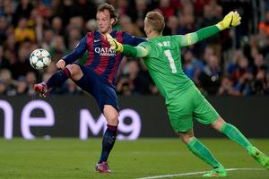 Ivan Rakitic of Barcelona lifts the ball over Manchester City's Joe Hart for the only goal of the game at the Nou Camp last night