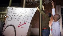 """Protesters hang up a flag which reads, """"Racism lives here"""", above a depiction of St. Louis, Missouri, outside the City of Ferguson Police Department and Municipal Court in Ferguson Missouri, March 11, 2015. The police chief of Ferguson, Missouri, resigned on Wednesday, following a scathing U.S. Justice Department report that found widespread racially biased abuses in the city's police department and municipal court.  Protesters had called for Chief Thomas Jackson's removal since the fatal shooting of an unarmed black teenager by a white Ferguson police officer on August 9. The killing triggered nationwide protests and drew scrutiny to police use of deadly force, especially against black men. REUTERS/Kate Munsch  (UNITED STATES - Tags: CRIME LAW POLITICS)"""
