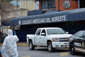 A forensic investigator walks outside a private school in Monterrey, Mexico, Wednesday, Jan. 18, 2016. A 15-year-old student opened fire with a gun at the school, hitting a teacher and two other students in the head before killing himself. (AP Photo/Emilio Vazquez)