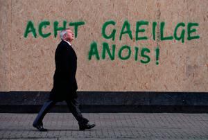 A man walks past graffiti in Belfast calling for an Irish-language act in the North. Photo: PA