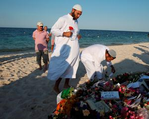 Residents of the coastal town of Sousse in Tunisia place flowers and messages during a gathering at the scene of Friday's shooting attack, Sunday, June 28, 2015