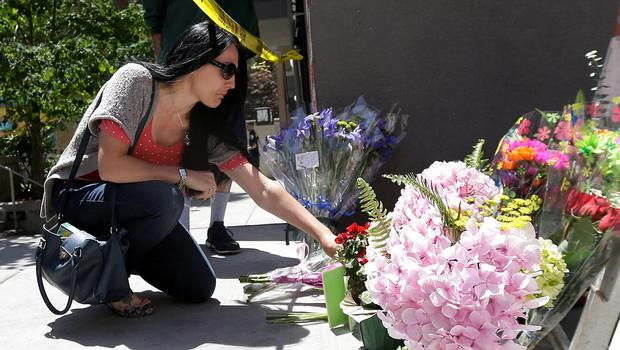 A woman leaves flowers at a makeshift memorial for victims of a balcony that collapsed in Berkeley, Calif., Tuesday, June 16, 2015. Berkeley police said several people were killed and others injured after a balcony fell shortly before 1 a.m., near the University of California, Berkeley. (AP Photo/Jeff Chiu)