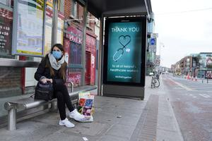 A woman wearing a protective face mask waits at a bus stop which displays a message of 'Thank you to Ireland's healthcare workers' in Dublin. Photo: REUTERS/Clodagh Kilcoyne