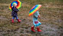 Daisy Martineau (R), aged three and her two-year-old sister Pheobe walk in the rain at Worthy Farm in Somerset during the Glastonbury Festival in Britain, June 28, 2015.  REUTERS/Dylan Martinez