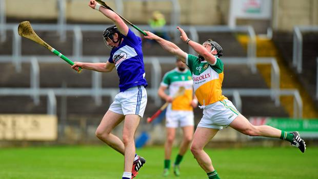 Joe Campion, Laois, goes up against Offaly's Sean Ryan