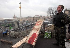 An anti-government protester stands near a blood stained stretcher during clashes with riot police in Kiev