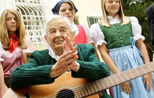 Maria von Trapp, daughter of Austrian Baron Georg von Trapp, prepares to play a guitar and sing with traditionally dressed children in front of her former home, Villa Trapp, in Salzburg in this July 24, 2008 file photo. Maria von Trapp, a member of the Austrian family whose escape from Nazi Germany and subsequent musical career inspired the famed musical The Sound of Music, has died at the age of 99, according to newspapers quoting her brother.