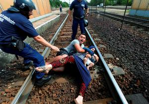 Hungarian policemen stand by the family of migrants protesting on the tracks at the railway station in the town of Bicske, Hungary, September 3, 2015.          REUTERS/Laszlo Balogh