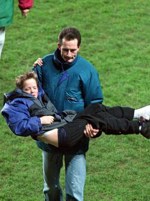 A young child is carried to safety after rioting broke out in 1995