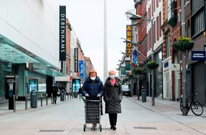 Two women wearing face masks on an almost deserted Henry Street yesterday. Photo: Brian Lawless/PA Wire