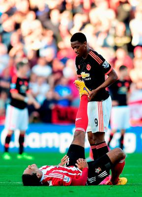 Anthony Martial of Manchester United assists a pained Virgil van Dijk