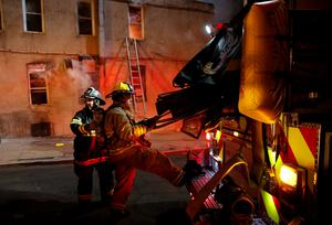 Baltimore firefighters pulls hoses from their truck to attack a fire set by rioters in a convenience store and residence on East Biddle street at Montford Avenue during rioting in Baltimore, Maryland in the early morning hours of April 28, 2015. REUTERS/Jim Bourg