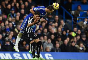 Chelsea's John Terry (L) climbs above Newcastle United's Spanish striker Ayoze Perez (R) to head the ball clear.
