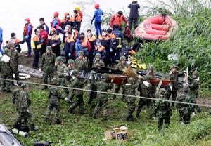 Rescuers and soldiers remove airplane parts after a TransAsia plane crashed into a river in New Taipei City. Reuters/Pichi Chuang