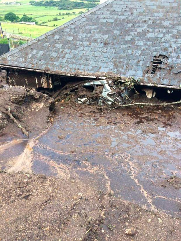 A car is sent through the back of Bernie Kearney's bungalow by a mudslide in Urris, north Donegal. Photo: Joe Boland