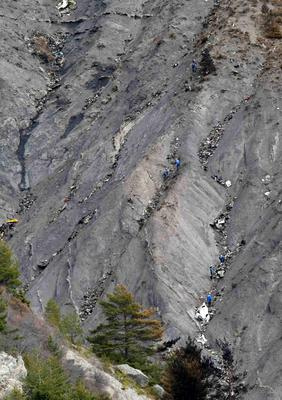 Rescue workers are seen near debris at the crash site of the Germanwings Airbus A320 near Seyne-les-Alpes, French Alps, March 30, 2015. REUTERS/Claude Paris/Pool