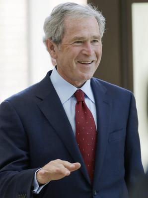 Former President George W. Bush arrives at the signing ceremony for the joint use agreement between the National Archive and the George W. Bush Presidential Center