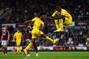 LONDON, ENGLAND - SEPTEMBER 20:  Raheem Sterling of Liverpool scores is team's first goal as teammate Mario Balotelli of Liverpool jumps to avoid the shot during the Barclays Premier League match between West Ham United and Liverpool at Boleyn Ground on September 20, 2014 in London, England.  (Photo by Mike Hewitt/Getty Images)