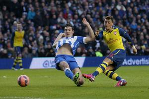 Arsenal?s Mesut Ozil, right, beats Brighton?s Lewis Dunk to score a goal, during the English FA Cup 4th round soccer match between Brighton & Hove Albion and Arsenal, at the Amex Stadium, Brighton, England, Sunday, Jan. 25, 2015. (AP Photo/Tim Ireland)