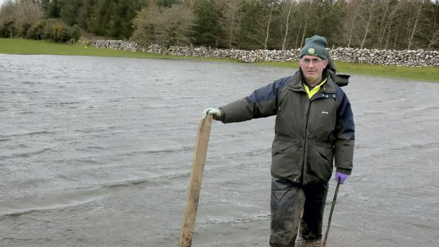 Knee deep: PJ Finnerty on his flooded farm in Kilcar, Co. Roscommon. PJ's farm is ten miles from the Shannon but all the river's tributaries are full and there are turloughs filling across the area. Photograph: Hany Marzouk