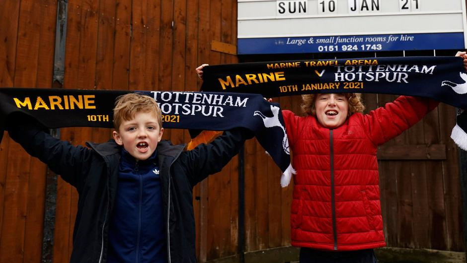 Two local young Marine FC fans pose for a photograph with their match day scarves in front of the club's board displaying their next home game against Tottenham in the FA Cup. Photo: Getty Images