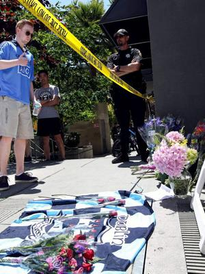 A man makes the sign of the cross over his heart after laying a bouquet of flowers near the scene of a 4th-story apartment building balcony collapse in Berkeley, California June 16, 2015. REUTERS/Elijah Nouvelage