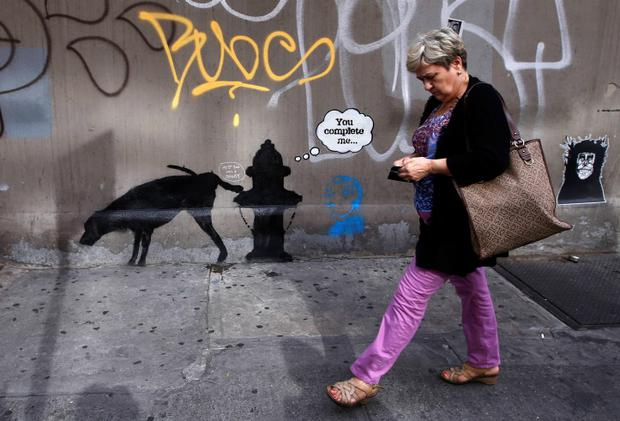 A woman walks past a new work by British graffiti artist Banksy on West 24th street in New York City