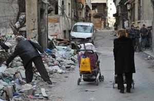 A Syrian man looks for items amid debris and garbage as he walks alongside a woman pushing a cart in a street of a besieged rebel-held area of Syria's third city Homs on February 11, 2014.