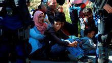 Migrants are detained by riot police in Hungary after crossing the border with Serbia