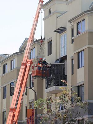 Workers with BELFOR Restoration Company look at a fourth floor balcony railing as it rests on the balcony below at the Library Gardens apartment complex in Berkeley, Calif. on Tuesday, June 16, 2015. Berkeley police say several people are dead and others injured after a balcony fell shortly before 1 a.m., near the University of California, Berkeley. (AP Photo/Jeff Chiu)