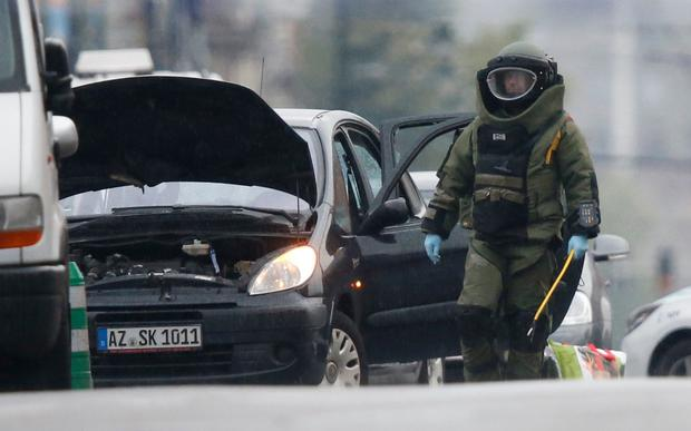 A bomb disposal squad is deployed after Belgian police shot at a vehicle in the Brussels district of Molenbeek Credit: REUTERS
