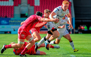 Rory Scholes, Ulster, on his way to score a try for his side, despite the tackle of James Davies, Scarlets