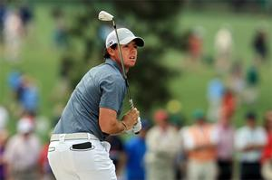 Rory McIlroy reacts after he hits a shot on the first hole