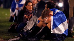 "Supporters from the ""Yes"" Campaign react as they sit in George Square in Glasgow"