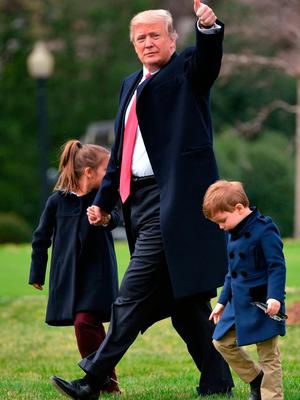 US President Donald Trump makes his way to board Marine One with grandchildren Arabella Kushner (L) and Joseph Kushner, from the South Lawn of the White House in Washington, DC on March 3, 2017.