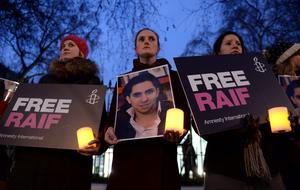 Protesters during an Amnesty International candle-lit protest vigil for blogger and free speech activist Raif Badawi outside the Saudi Arabia Embassy (Anthony Devlin/PA Wire)