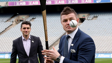 Bernard Brogan looks on as Brian O'Driscoll shows off his hurling skills during the World Rugby Technical Review Group's visit to Croke Park. Photo: INPHO