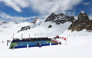 Swiss tennis player Roger Federer (L) serves a ball to U.S. skier Lindsey Vonn during a promotional tennis event on the Aletsch glacier at the Jungfraujoch. The world number three and the Alpine skiing champion played on a specially prepared tennis court on a glacier at an altitude of 3475 m (11401 feet). REUTERS/Denis Balibouse