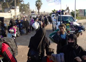 United Nations and Red Crescent vehicles loaded with suitcases escort Syrian civilians evacuated from the besieged Syrian city of Homs, on February 9, 2014.